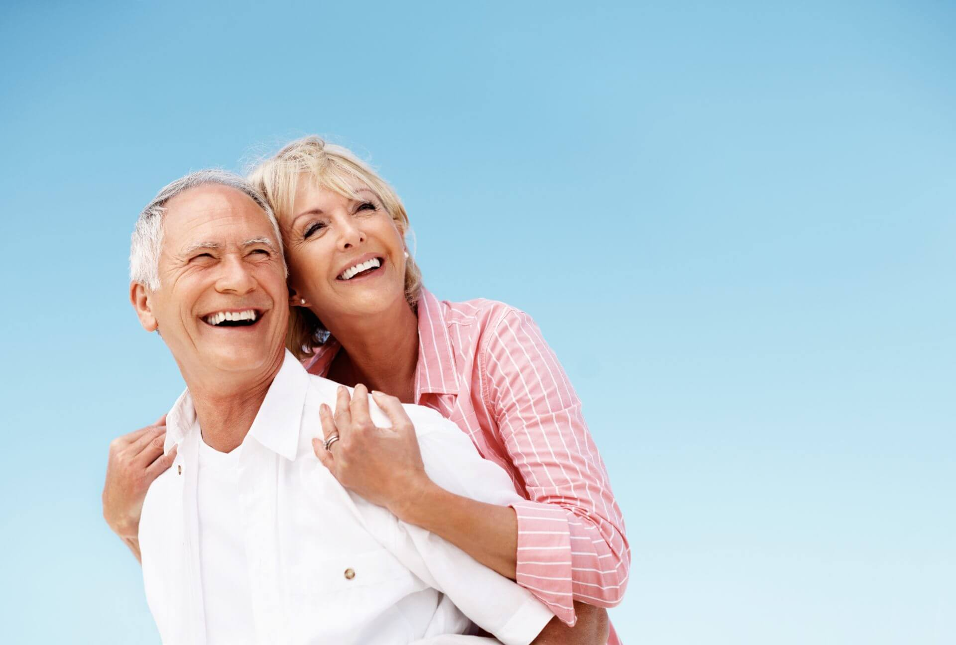 Senior couple piggybacking happily against blue sky - copyspace